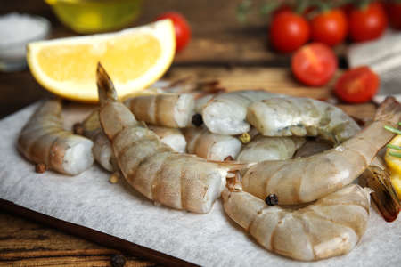 Fresh raw shrimps with lemon on wooden board, closeup