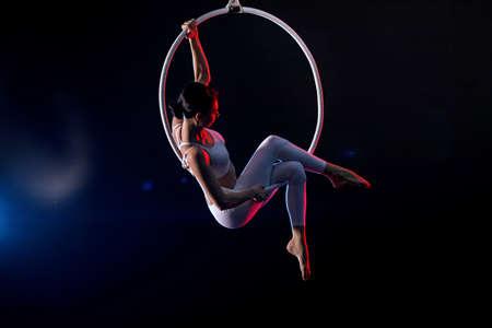 Jeune femme exécutant l'élément acrobatique sur l'anneau aérien sur le fond foncé