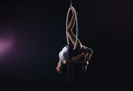 Young woman performing acrobatic element on aerial ring against dark background. Space for text