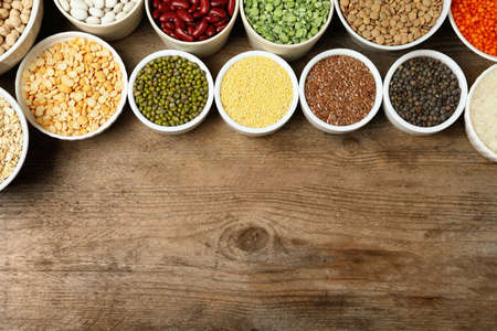 Different grains and cereals on wooden table, flat lay. Space for text