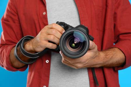 Professional photographer working on light blue background in studio, closeup 免版税图像