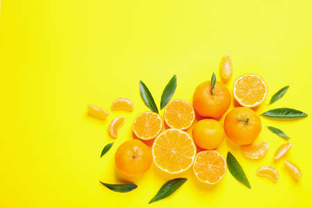Flat lay composition with fresh ripe tangerines and leaves on yellow background. Citrus fruit Stockfoto