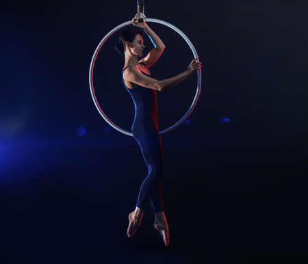 Young woman performing acrobatic element on aerial ring against dark background 版權商用圖片