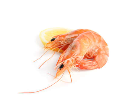 Délicieuses crevettes cuites et citron isolés sur blanc
