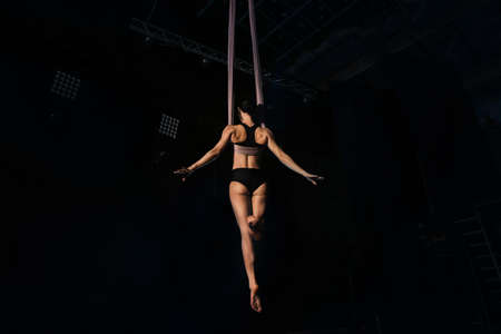 Young woman performing acrobatic element on aerial silk indoors