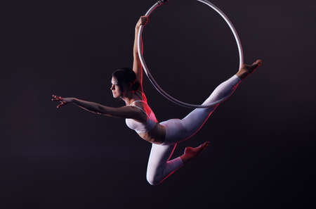 Young woman performing acrobatic element on aerial ring indoors