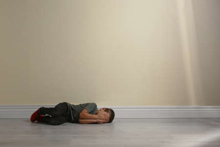 Little boy closing face with hands lying on floor near yellow wall, space for text. Child in danger