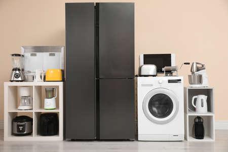 Réfrigérateur moderne et autres appareils ménagers près du mur beige à l'intérieur