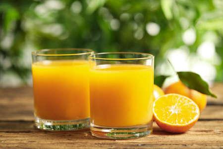 Vasos de jugo de mandarina fresco y frutas en la mesa de madera