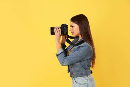 Fotógrafo profesional trabajando sobre fondo amarillo en estudio