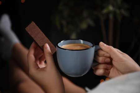 Mujer con oblea y café sobre fondo oscuro, primer plano. Desayuno temprano