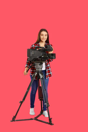 Operator with professional video camera on pink background