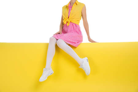 Woman wearing white tights sitting on color background, closeup