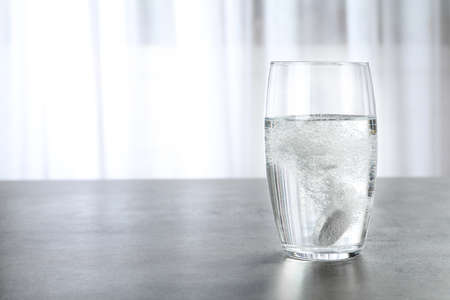 Glass with effervescent tablet on grey table indoors, space for text. Medical care Imagens