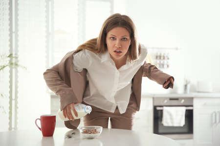 Giovane donna che cucina in fretta la colazione a casa. Preparativi mattutini Archivio Fotografico