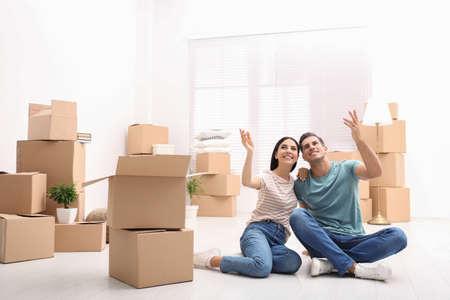 Pareja feliz en la habitación con cajas de cartón el día de la mudanza