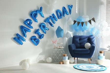 Frase FELIZ CUMPLEAÑOS hecha de letras de globo azul en habitación decorada Foto de archivo