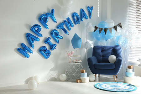 Phrase HAPPY BIRTHDAY made of blue balloon letters in decorated room Imagens