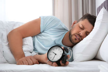 Sleepy man with alarm clock at home in morning Imagens