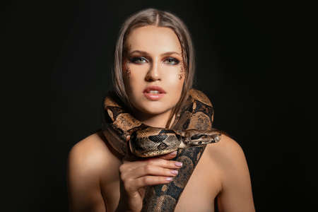 Beautiful woman with boa constrictor on black background 写真素材