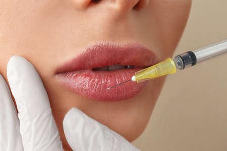 Woman getting lip injection on beige background, closeup Reklamní fotografie