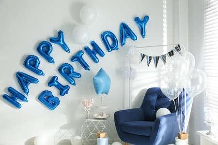 Frase FELIZ CUMPLEAÑOS hecha de letras de globo azul en habitación decorada