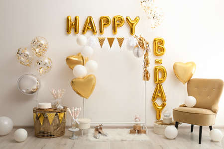 Phrase HAPPY BIRTHDAY made of golden balloon letters in decorated room Standard-Bild