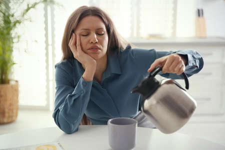 Sleepy young woman pouring coffee into cup at home in morning