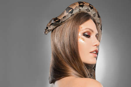 Beautiful woman with boa constrictor on light grey background