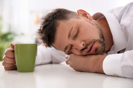 Man with cup of drink sleeping at home in morning