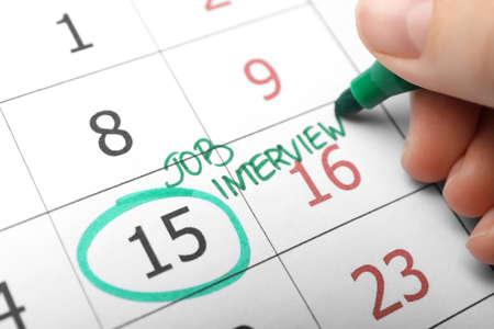 Woman marking date of job interview in calendar, closeup