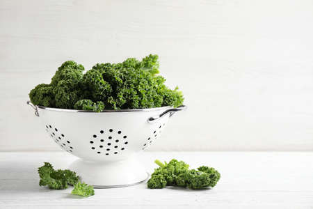 Fresh kale leaves on white wooden table. Space for text