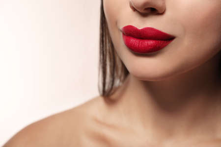 Woman with red lipstick on light background, closeup