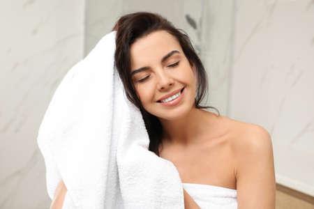 Junge Frau trocknet Haare mit Handtuch im Badezimmer