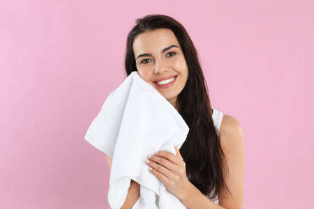 Young woman wiping face with towel on pink background