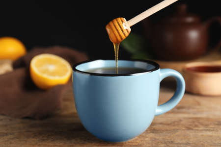 Honey dripping into cup of tea on wooden table