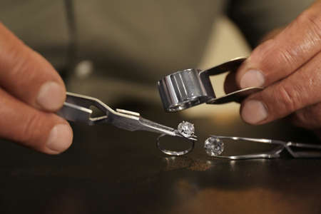 Professional jeweler working with beautiful ring at table, closeup