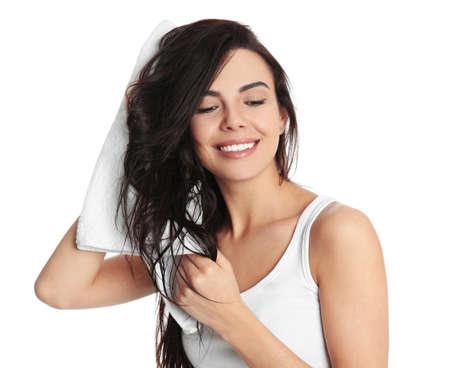 Mujer joven secar el cabello con una toalla sobre fondo blanco.