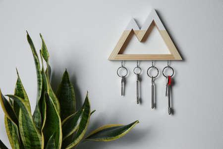 Wooden key holder on light wall indoors