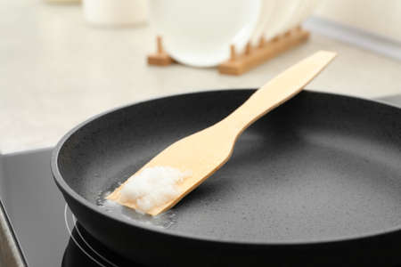 Frying pan with coconut oil on induction stove, closeup. Healthy cooking Foto de archivo