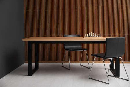 Mesa moderna con ajedrez junto a la pared de madera Foto de archivo