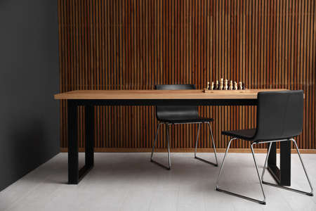 Modern table with chess near wooden wall Reklamní fotografie