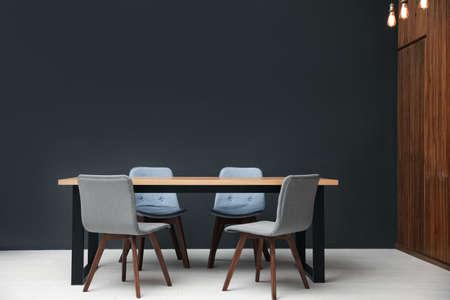 Modern empty wooden table near black wall