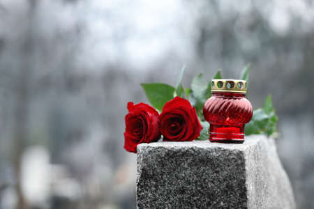 Red roses and candle on grey granite tombstone outdoors. Funeral ceremony