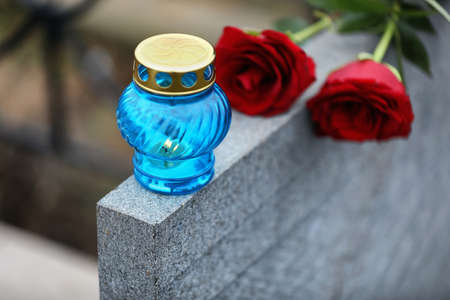 Red roses and candle on light grey tombstone outdoors, closeup. Funeral ceremony