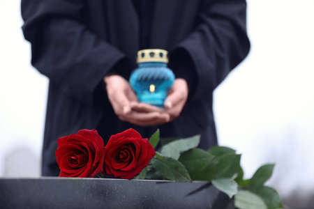 Woman with candle outdoors, focus on red roses. Funeral ceremony 스톡 콘텐츠