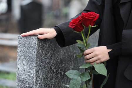 Woman with red roses near grey granite tombstone outdoors, closeup. Funeral ceremony 스톡 콘텐츠