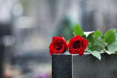 Rose rosse sulla pietra tombale di granito nero all'aperto. Cerimonia funebre