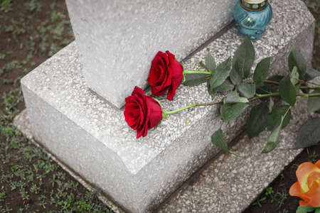 Red roses and candle on old grey tombstone outdoors. Funeral ceremony