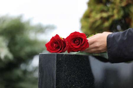 Mujer con rosas rojas cerca de lápida de granito negro al aire libre, primer plano. Ceremonia funeral